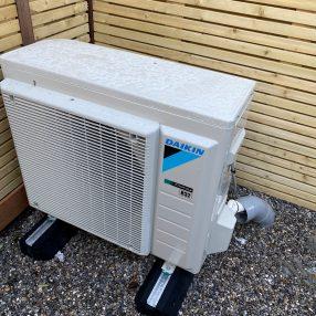 de in achter in onze tuin geplaatste luchtwarmptepomp. Deze zal over een aantal weken nog worden 'omkast' om het zicht en geluid te verbeteren.